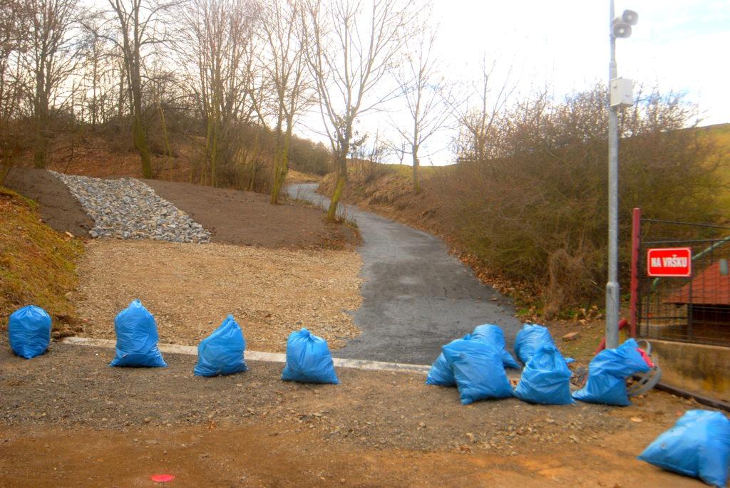 Cesta do horního resortu má nový provizorní povrch. Vlevo od cesty vsakovací průleh a v popředí odpadky sesbírané v rokli